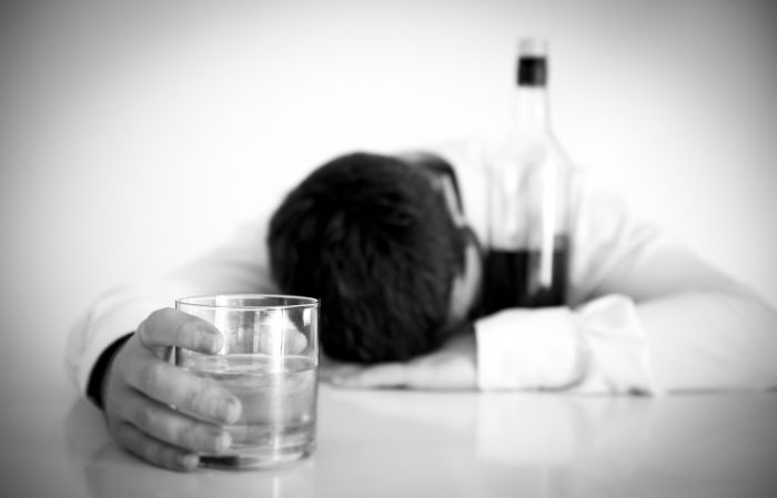 black and grey image of a businessman asleep with alcohol to symbolize executive mental-health and substance-abuse issues