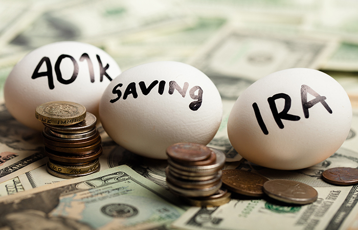 Eggs sitting on money with 401k, saving and IRA written on them to illustrate workers saving for retirement and whether they can live comfortably