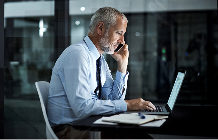Older man on the phone working at a laptop, so why are companies reluctant to hire older workers?
