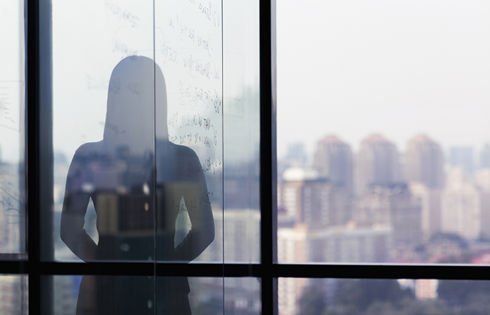 silhouette of a woman against the city backdrop represents the option to anonymously report incidents of sexual harassment