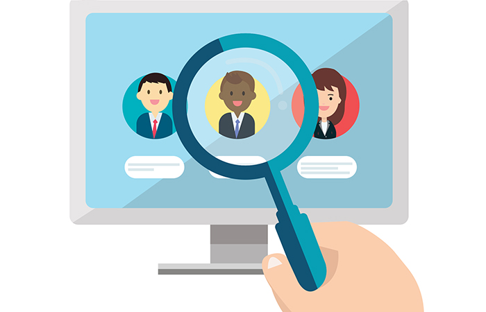 A magnifying glass over a candidate's face to measure quality of hire for employee-retention rates