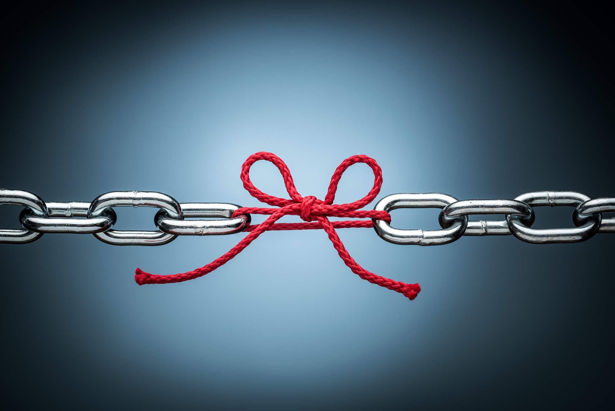 Two metal chains tied together with red string bow signifies the link between learning and strategy