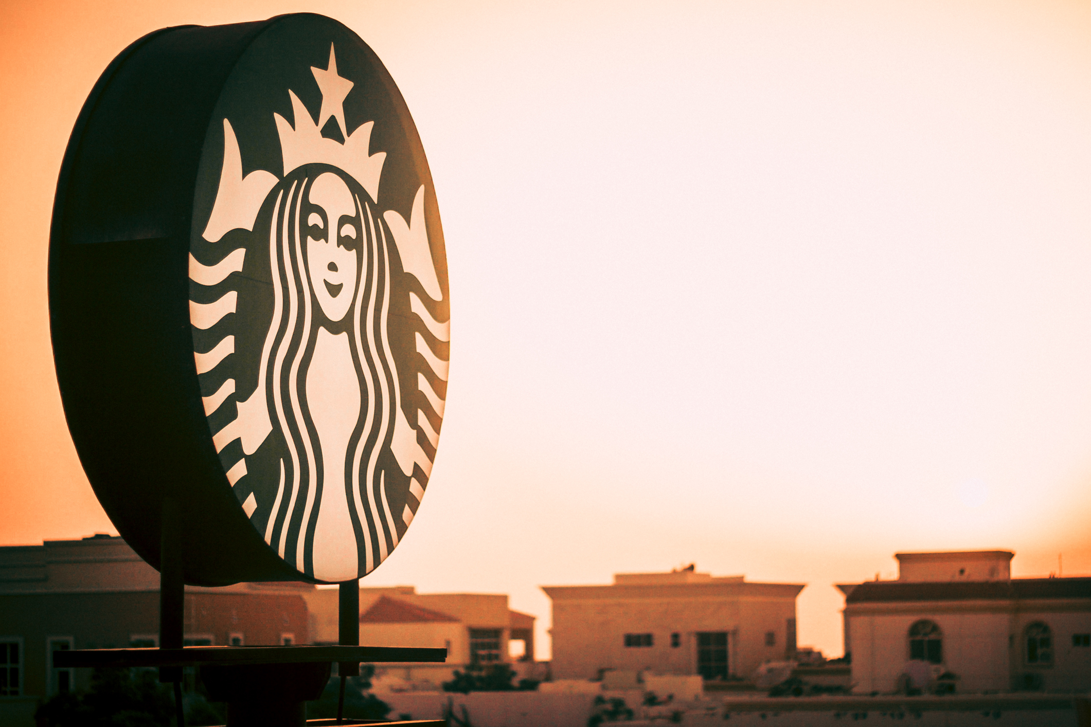 Sunset behind a giant starbucks sign to represent the stores closing for unconscious-bias training