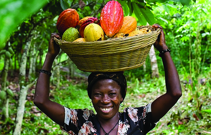 A happy, female cocoa farmer participating in the skills-exchange program