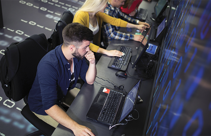 Arieal view of people working on laptops, AI disruptions