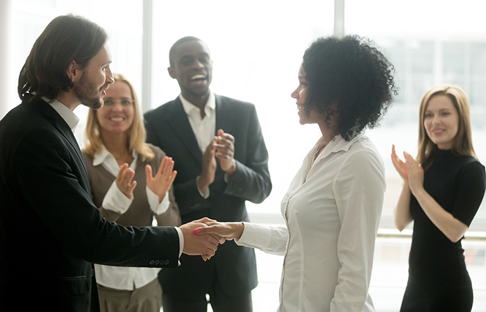 A boss shakes the hand of a woman while other employees applaud, showing how employee engagement is connected to recognition.