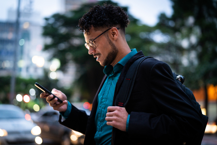 Business man with glasses checks his mobile phone