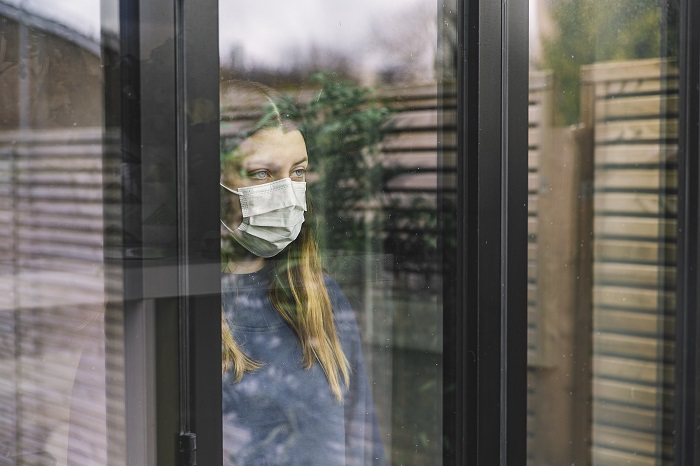 Teenage girl looking through window with mask